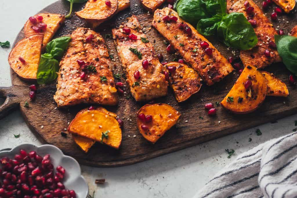 salmon on a cutting board with veggies and pomegranates