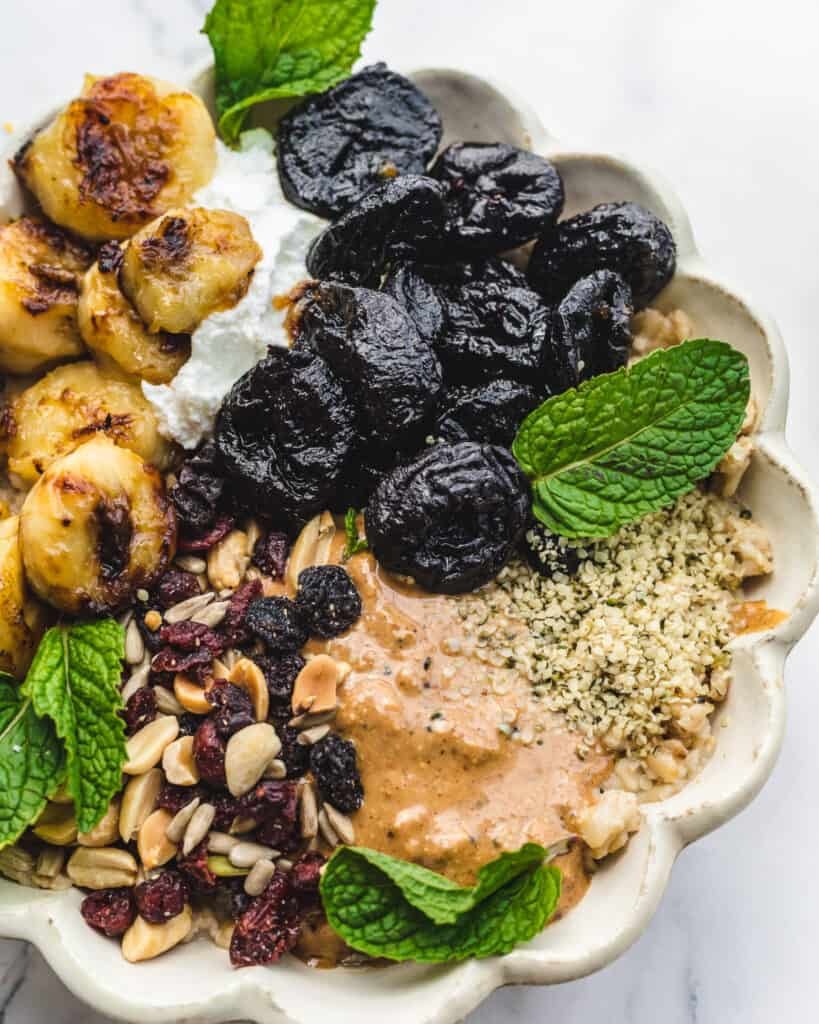 caramelized bananas and prunes with nut butter dried fruit on top of oatmeal
