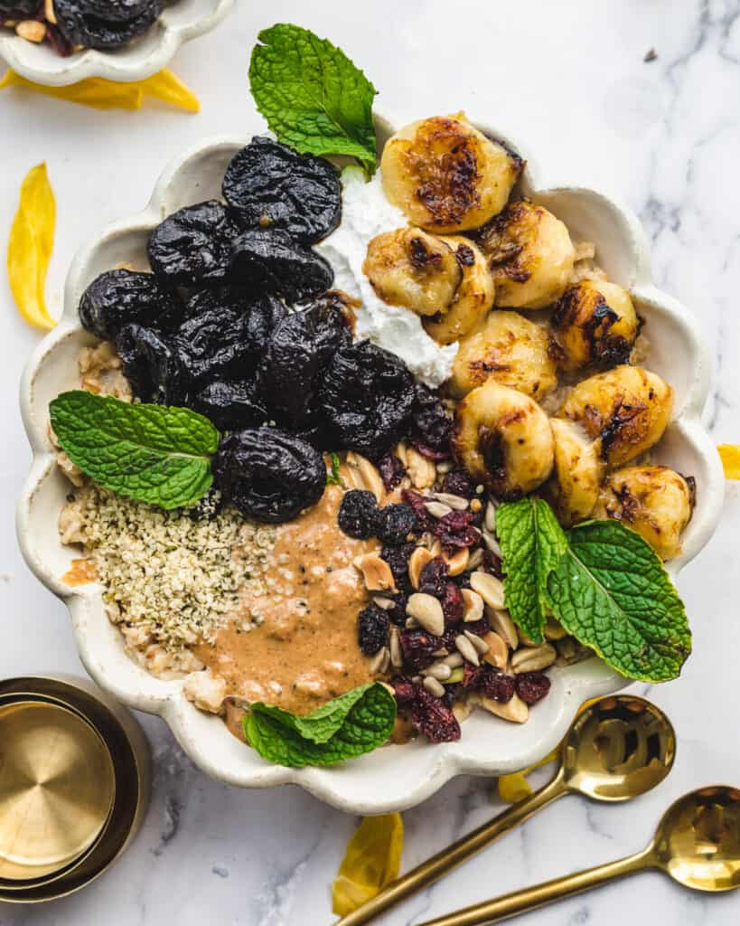caramelized bananas and prunes with nut butter dried fruit on top of oatmeal`