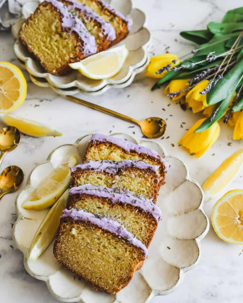 Lemon Olive Oil Loaf on a serving board with lavender and tulips topped with lavender mascarpone