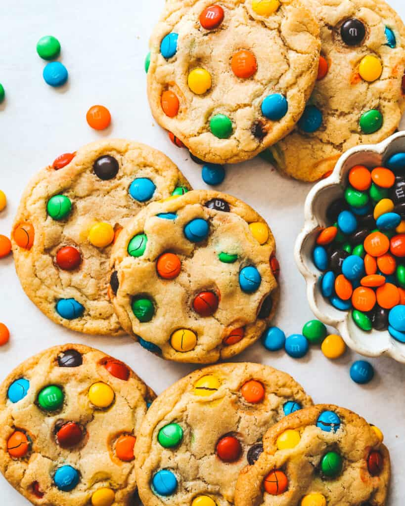 Chewy M&M Cookies laid on a flat surface with M&Ms in a bowl