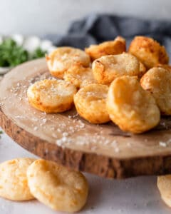 Pao De Queijo on a wooden cheese board with fresh herbs in the background