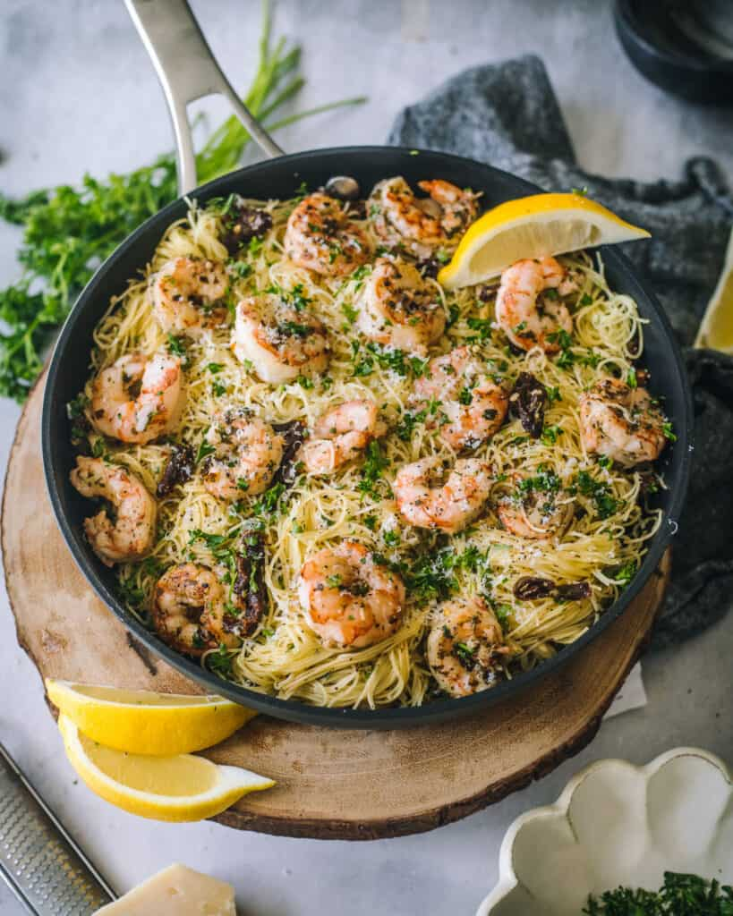 Pesto Shrimp Pasta with Sun-Dried Tomatoes in a skillet with parsley
