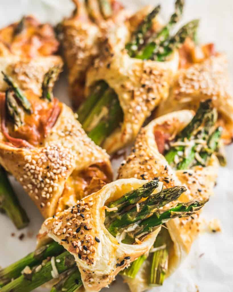 Asparagus and Prosciutto Puff Pastry Bundles on a piece of parchment paper