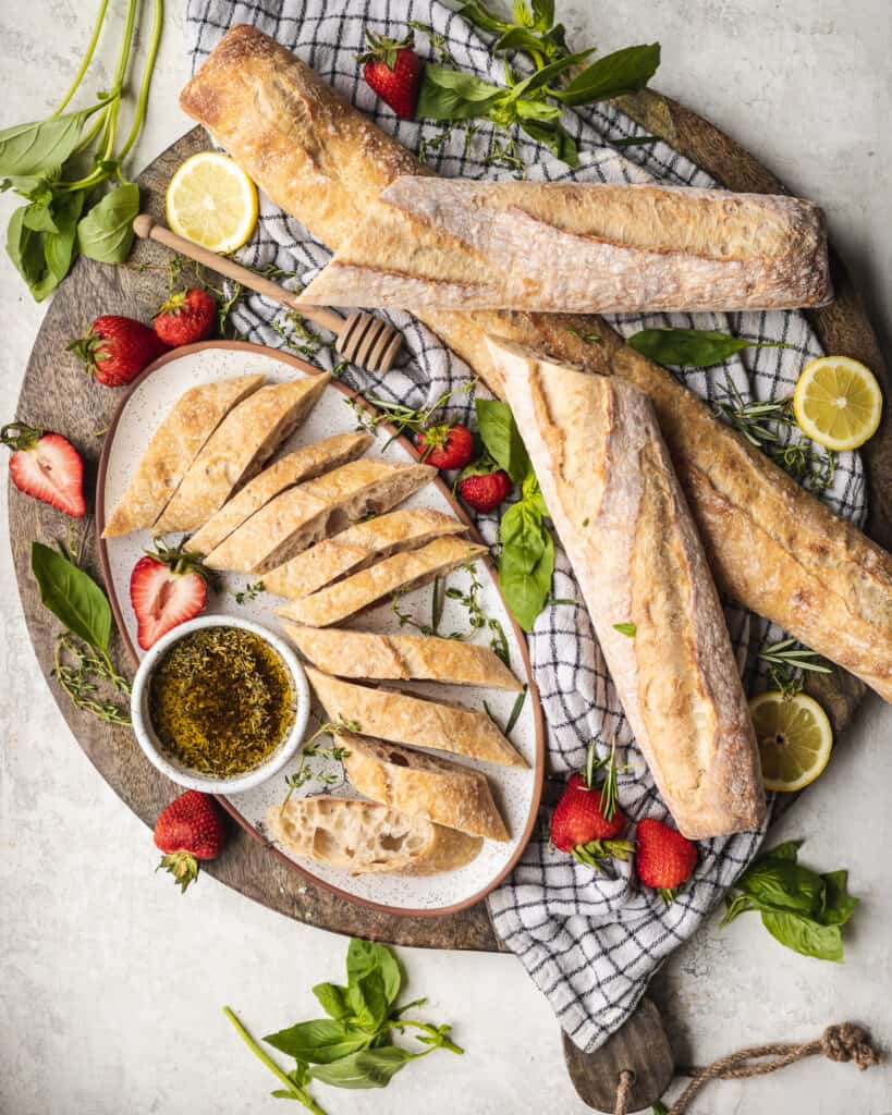 baguettes on a cutting board with strawberries and dipping oil