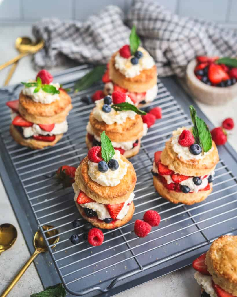 Mixed Berry Shortcakes with whipped mascarpone cream on a plate with a spoon