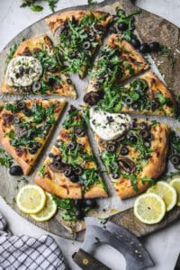 Cheesy Olive Pizza on a cutting board topped with arugula and burrata