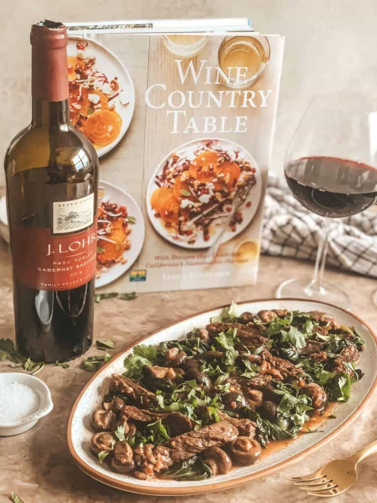 A plate of skirt steak with a cookbook in the background and a wine bottle and wine in wine glasses