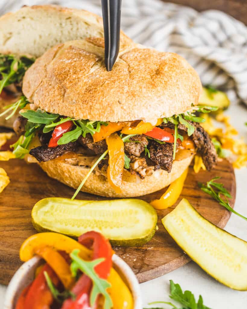 steak sandwich on a cutting board with chips and pickles