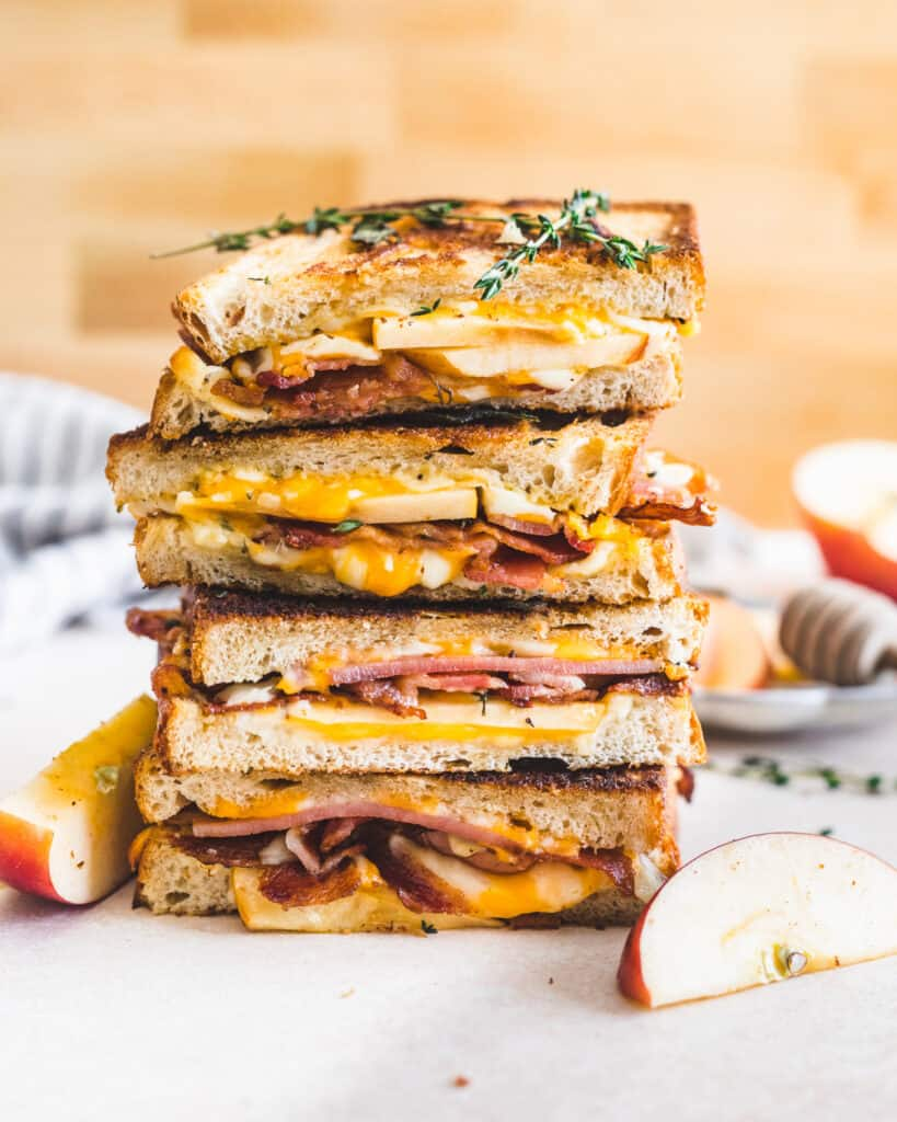 apple bacon cheddar grilled cheese cut in half and placed on top of each other