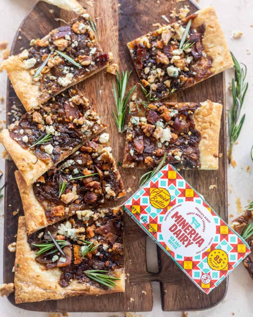Caramelized Onion Puff Pastry with bacon and gorgonzola on a cutting board with rosemary leaves with Minerva Dairy butter package