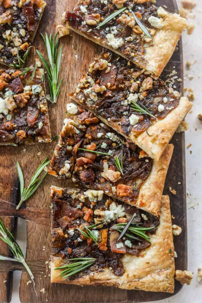 Caramelized Onion Puff Pastry with bacon and gorgonzola on a cutting board with rosemary leaves