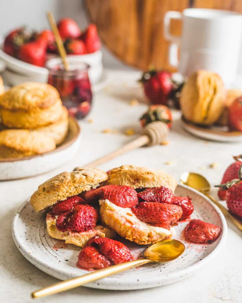 Honey Buttermilk Biscuits on a plate with strawberries and biscuits surrounding the plate