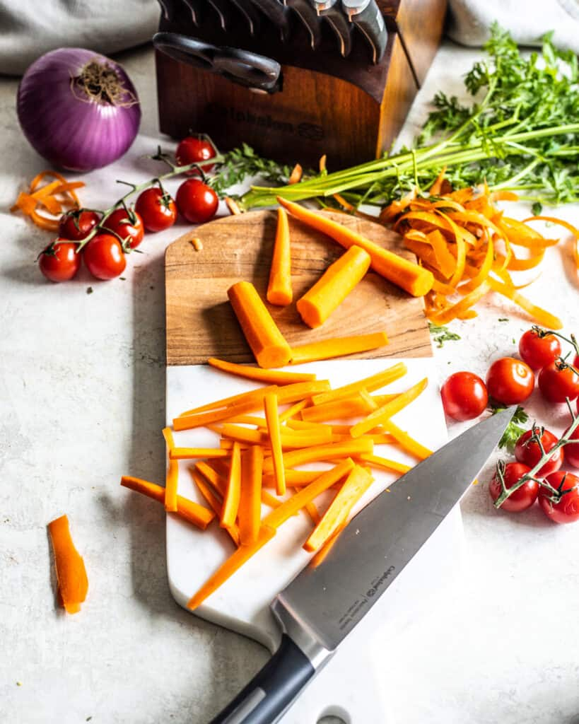 Julienne carrots on cutting board with a knife