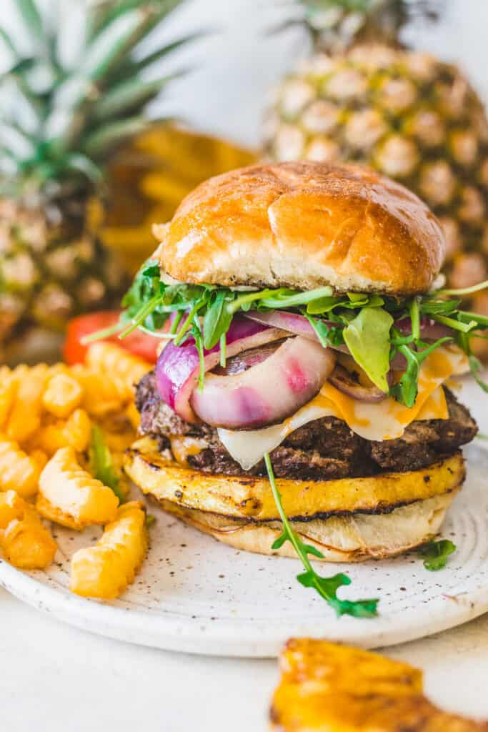 burger and fries on a plate with pineapples in the background