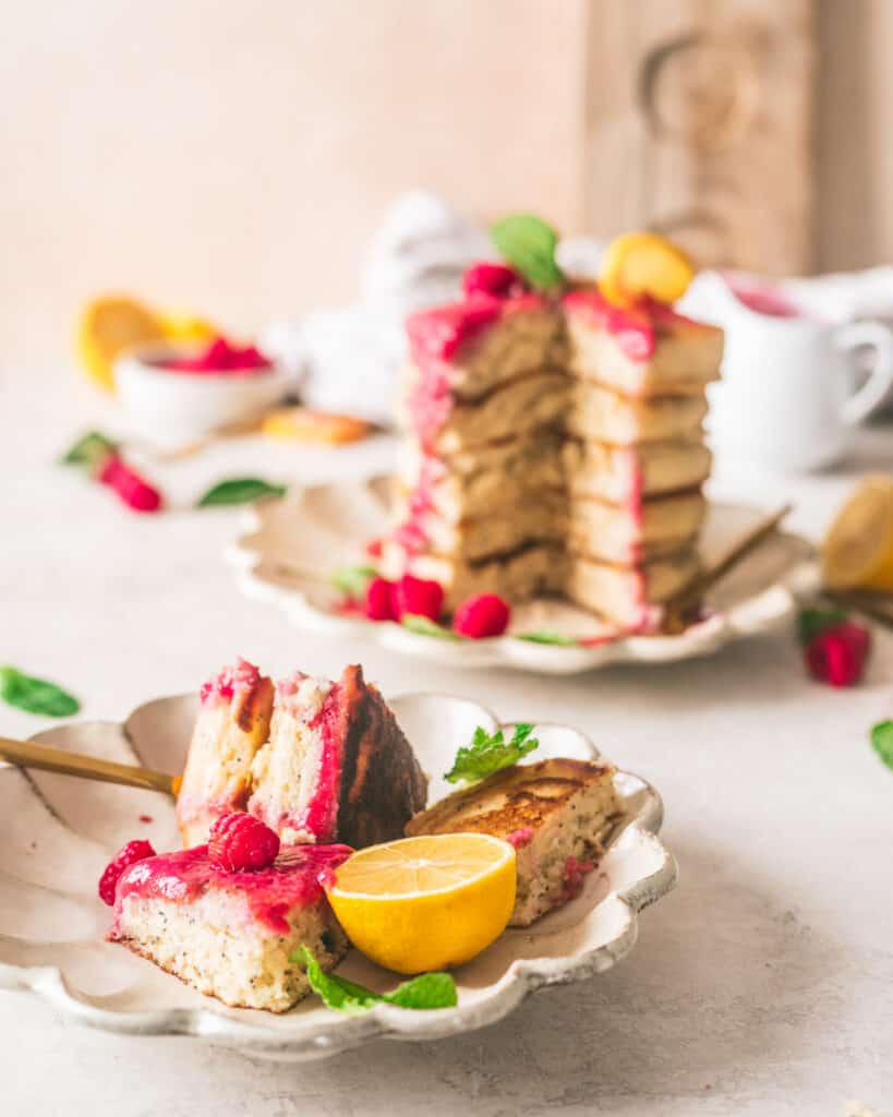 Lemon poppyseed pancakes on a plate with lemons and raspberries