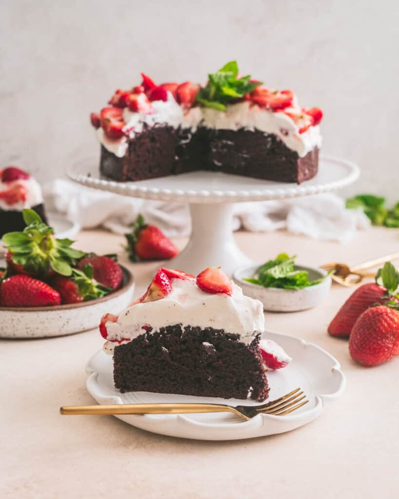 Chocolate cake on a plate with cake on cake stand in the background