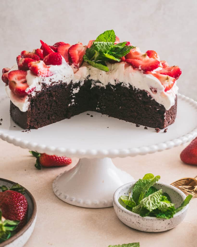 Strawberries and cream chocolate cake on a cake stand