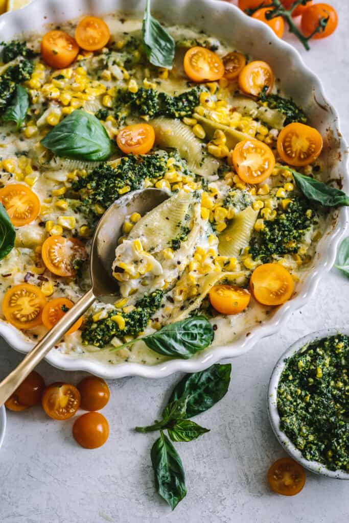 kale pesto and cheese stuffed shells in a baking dish with veggies around it
