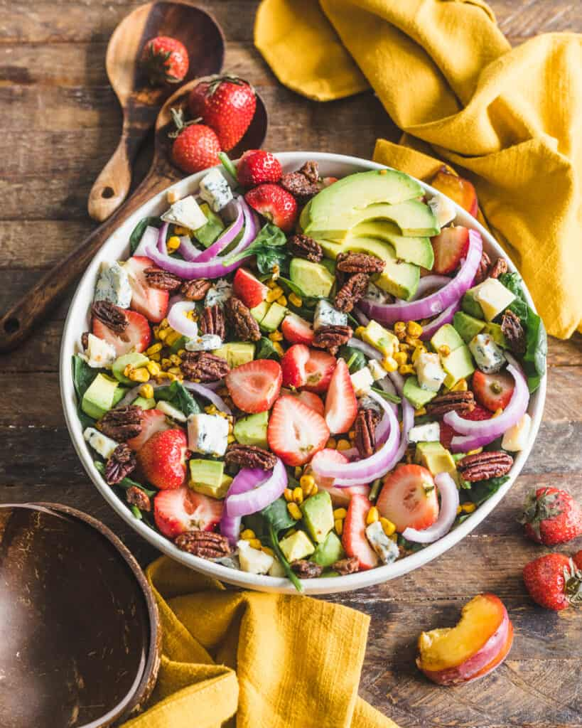 Salad on a wooden background with yellow napkins