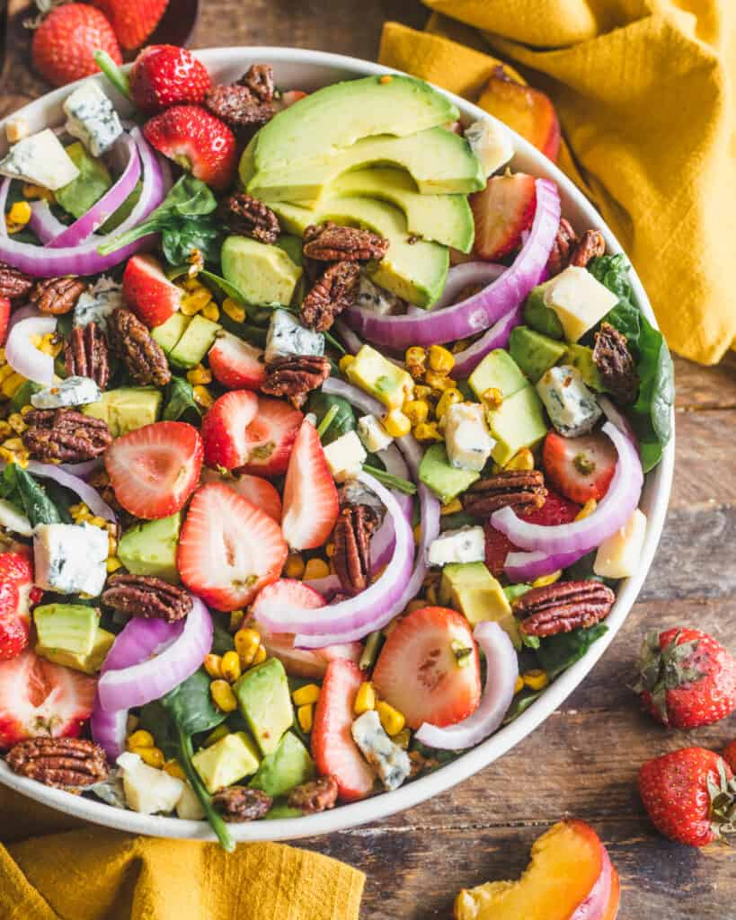 strawberry avocado spinach salad on a wooden surface