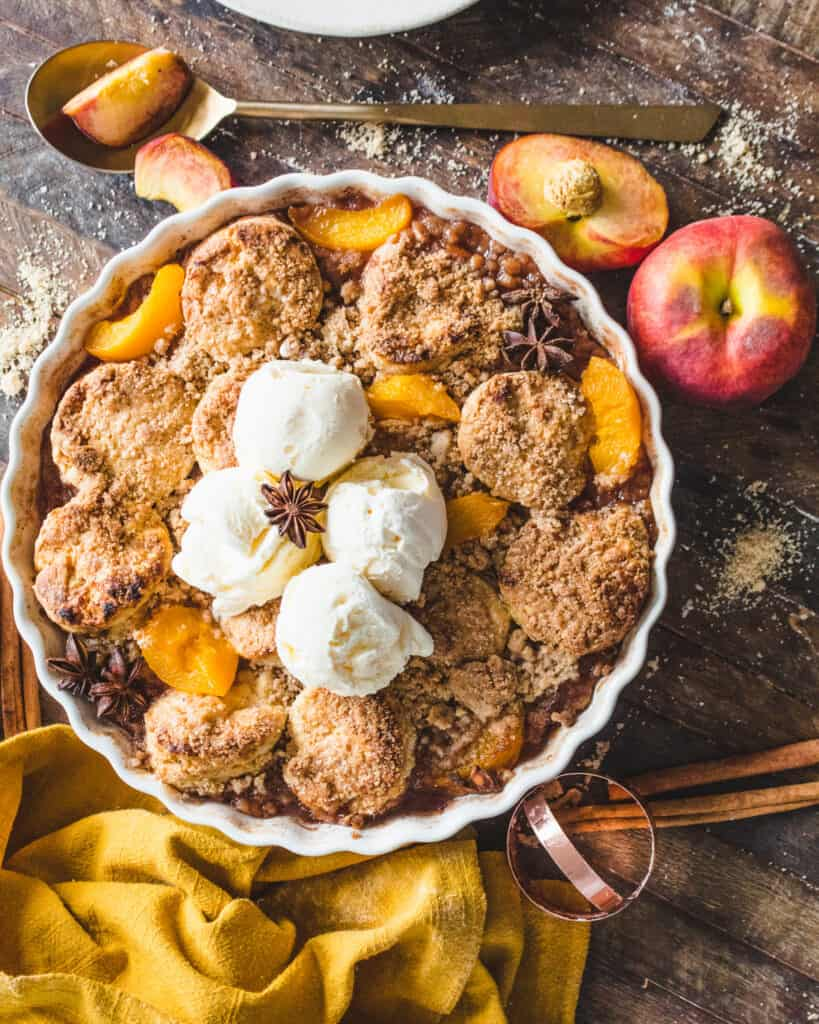 vegan peach cobbler with cinnamon streusel on a wooden surface with peaches and cloth around it