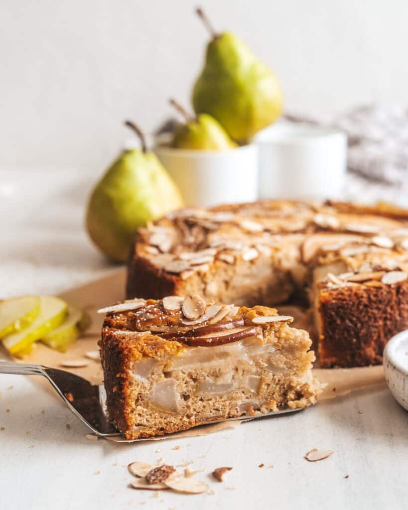 A slice of spiced pear and apple cake with pears in the background