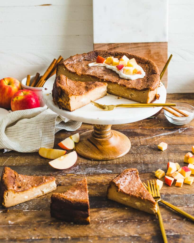 A sliced Apple Butter Basque Cheesecake with plates of individually sliced and plated cheesecakes in the foreground.