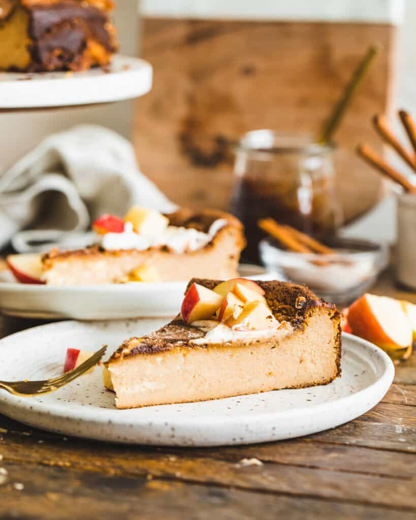 A plated slice of Apple Butter Basque Cheesecake with apple and whipped cream topping