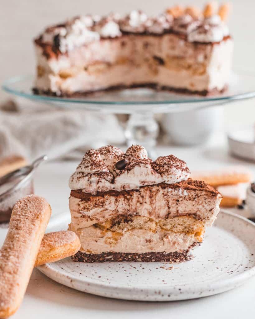 One slice of plated No-Bake Tiramisu Cheesecake alongside two ladyfingers.
