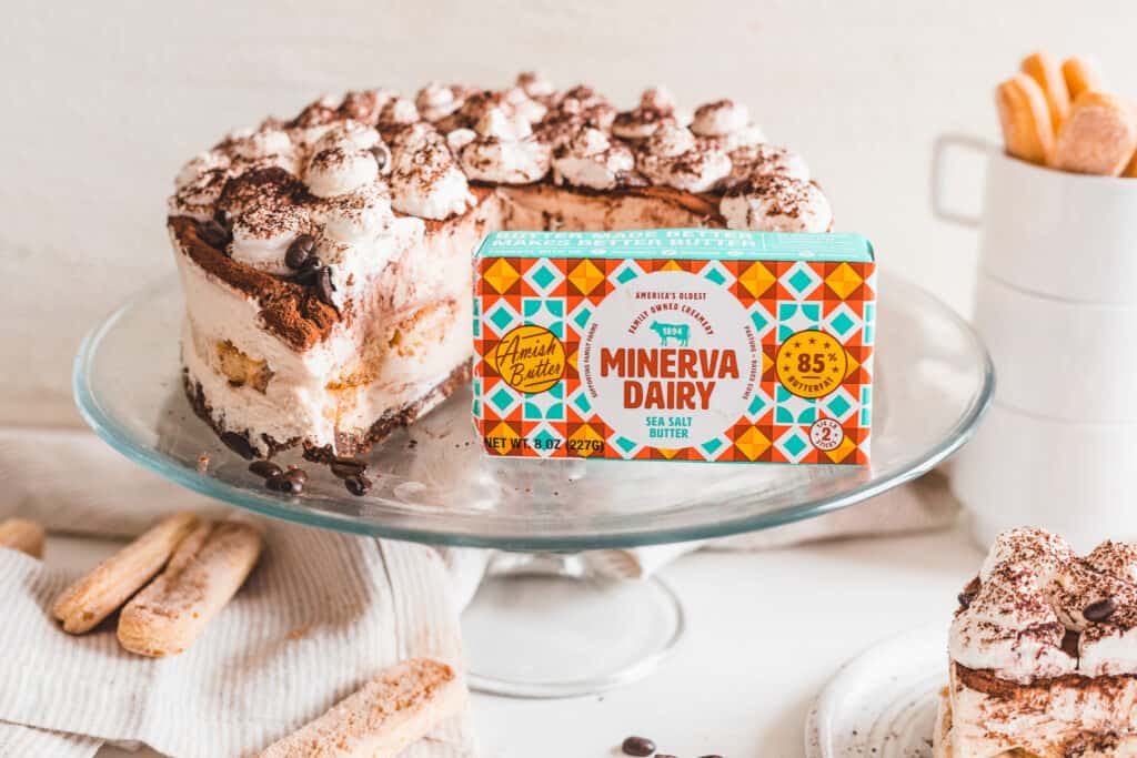 A sliced No-Bake Tiramisu Cheesecake on an elevated serving dish with an 8 ounce pack of Minerva Dairy Sea Salt Butter at the forefront.