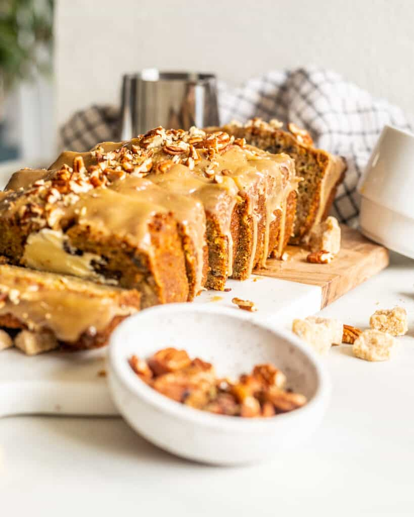 Sliced Zucchini Bread with Maple Glaze on a table with pecans