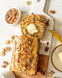 Zucchini Bread with Maple Glaze on a table with pecans