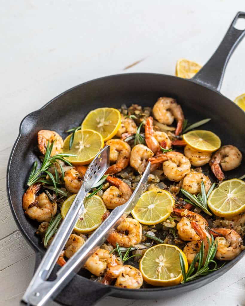 Shrimp in a cast iron skillet with lemons and herbs