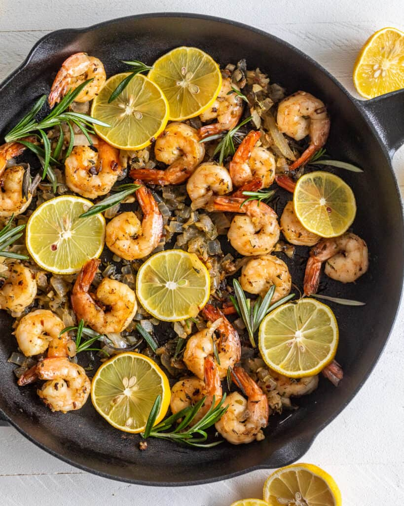 Shrimp on a cast iron skillet with lemons and herbs