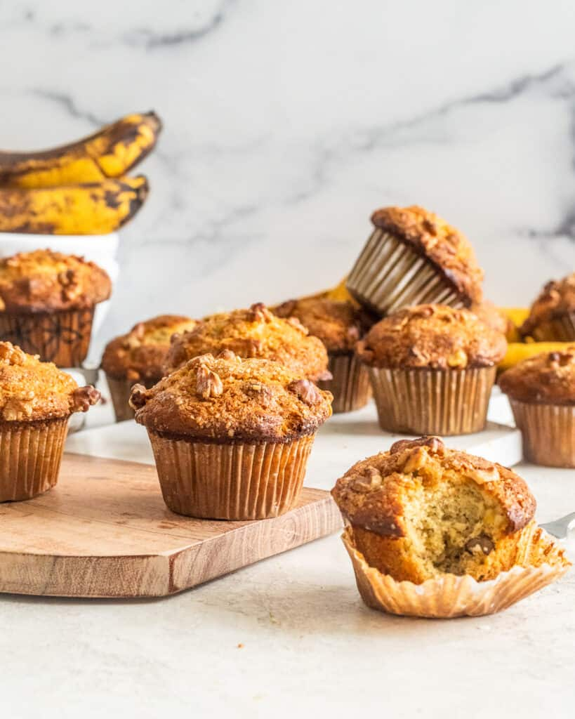 Scattered Banana Nut Muffins with ripe bananas in the background.