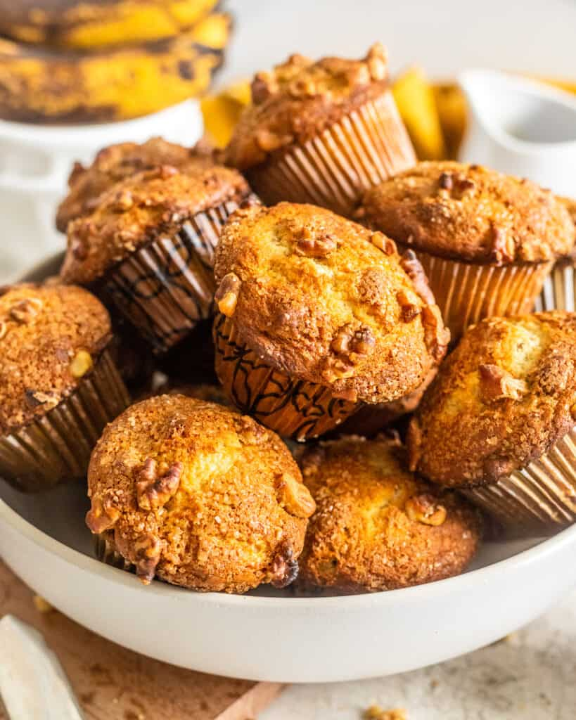 A white bowl full of banana nut muffins with bananas in the background.