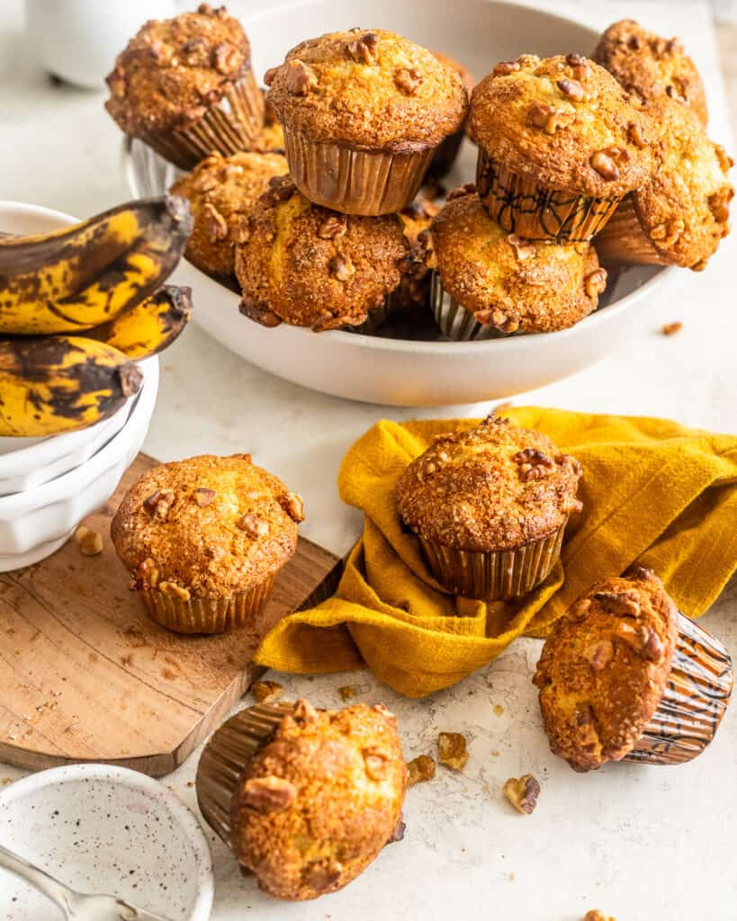 Scattered Banana Nut Muffins with a white bowl full of more muffins in the background and ripe bananas in another bowl off to the left.