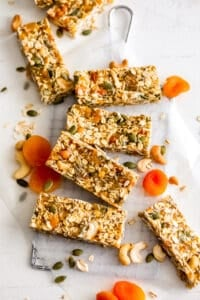 Apricot Coconut Cashew bars on a white surface with dried apricots and pumpkin seeds