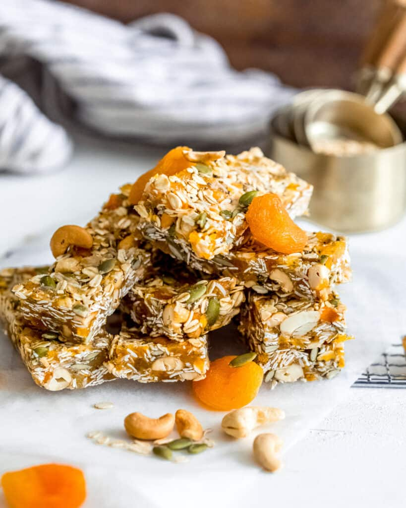 Apricot Coconut Cashew Bars piled on top of each other with oats in a measuring cup in the background