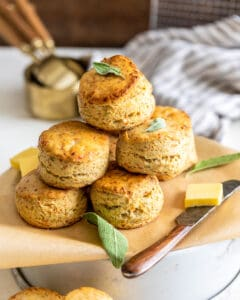 Sage Brown Butter Biscuits stacked on top of each other with measuring cups in the background