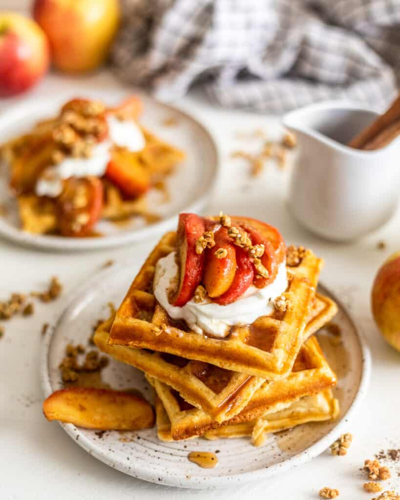 waffles on a plate with syrup and more waffles in the background
