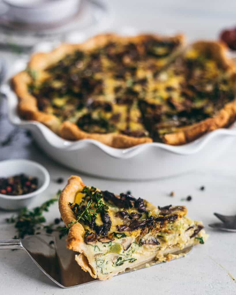 A slice of quiche in front of a pie pan full of the remainder of the quiche