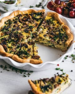 Kale and Mushroom quiche in a pie pan with a slice cut out of it
