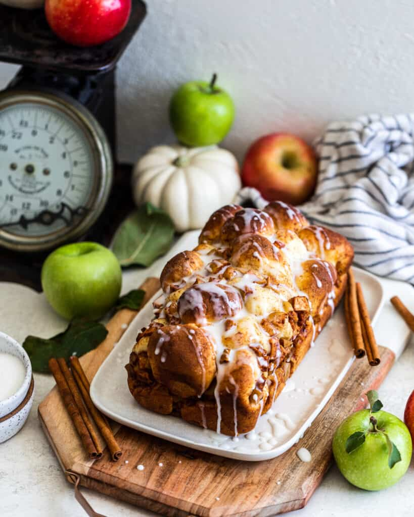 Apple and Pear Bread with apples and a pumpkin behind it