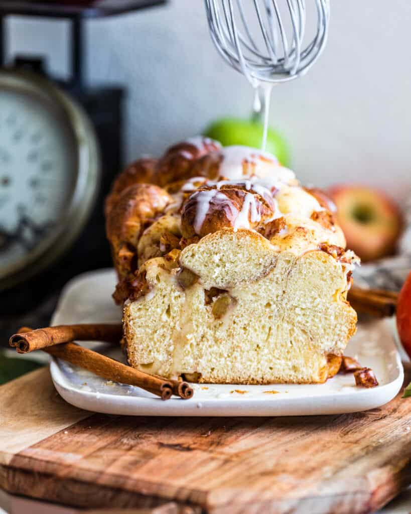 Apple and Pear Bread with whisk drizzling glaze on top