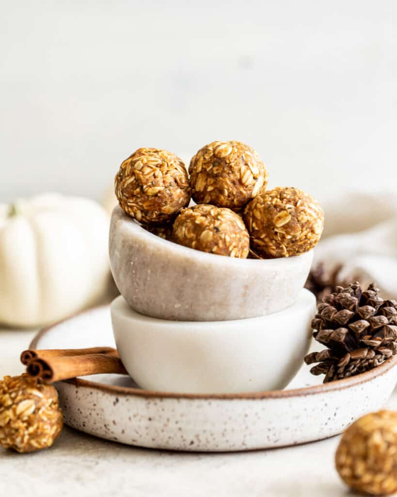 chai spiced energy bites in a bowl next to a pine cone