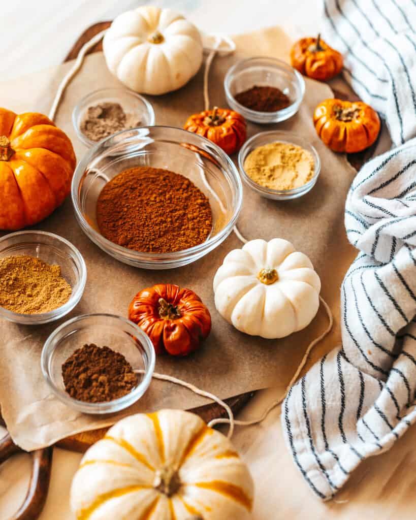 Overhead view of an assortment of the ingredients for the Spice recipe in glass bowls, along with an assortment of pumpkins and a striped blue and white cloth.