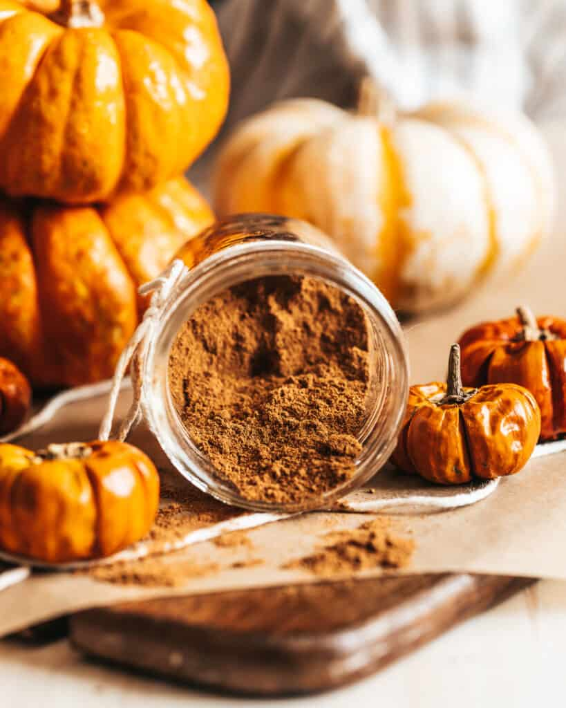 An open jar of Homemade Pumpkin Spice with some seasoning spilled on the table with an assortment of pumpkins in the background.