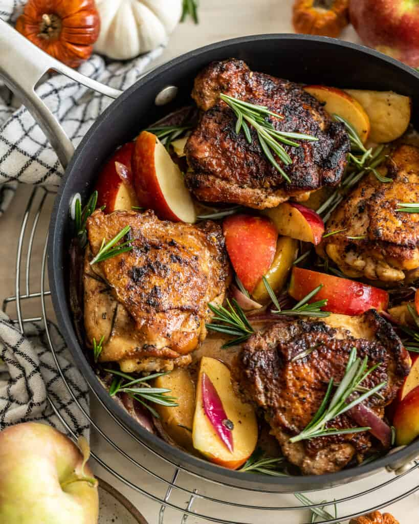 Rosemary Apple Cider Chicken in a pan surrounded by apples